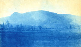 [View of mountains with large field in foreground]
