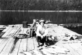 [Man posing with salmon catch on dock, Stuart Island, B.C.]