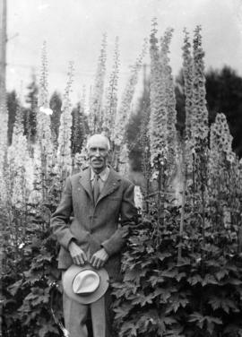 James L. Quiney [in front of delphiniums at] 4916 Union Street, Burnaby