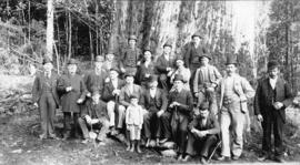 [Group of men and one boy in front of a large tree]