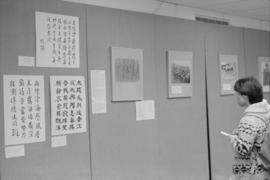 Visitor looking at items displayed at a historical photographs exhibit at the Chinese Cultural Ce...