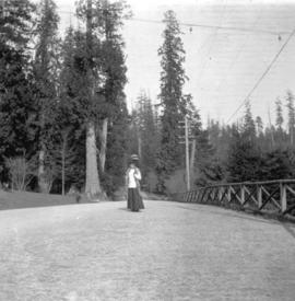 [Woman on path at entrance to Stanley Park]