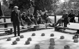 [Men playing giant checkers]