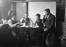 [Four men eating meal in Stuart Thomson's studio - Stuart Thomson on right]