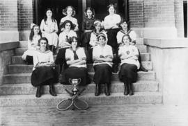Girls' tennis team seated on steps of brick school building