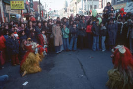 Spectators viewing colourful creatures in the Chinese New Year parade on Pender Street
