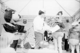 Tillicum, unidentified man and two chicken mascots on stage