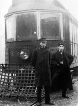 [Driver and conductor in front of a street car]
