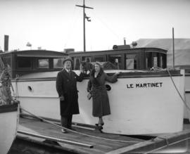 "Mr. McGachan [man, woman and small dog pose with boat ""Le Martinet""]"