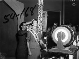 Man putting necklace on Nancy Hansen, Miss P.N.E., at Millers Jewelers draw in Manufacturers buil...