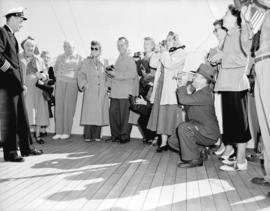 "Capt. Caldwell lectures [a group of passengers] on bridge of ""Prince George"""