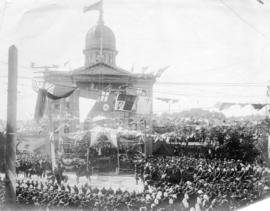 [The Duke and Duchess of Cornwall and York on podium in front of old courthouse on corner of Hast...