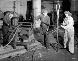 [A woman and men making steel cables]