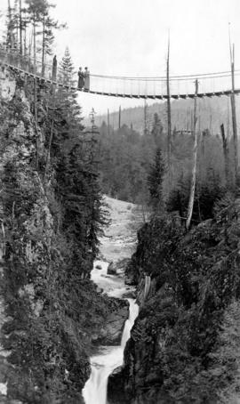 Suspension bridge with two women over Capilano Canyon