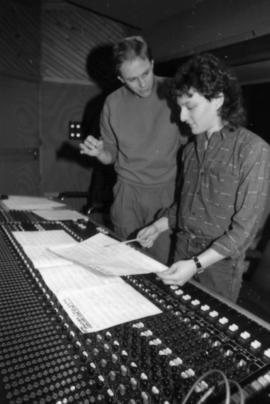 Two men behind audio mixing board