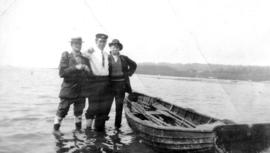 [Three men beside a rowboat]