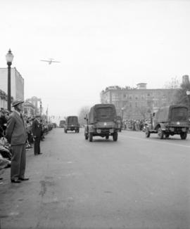 [Military trucks passing by crowds in a parade and an airplane flying above]