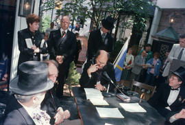 Mike Harcourt speaking into telephone during reenactment of Vancouver's first City Council meetin...