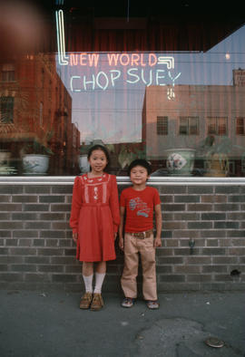 Two children standing outside New World Chop Suey in Edmonton Chinatown