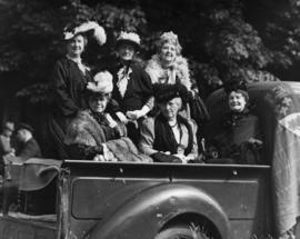 Six pioneer women in 1890's outfits seated in pick-up truck in a parade