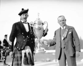 "Caledonian Games [two men with ""J.W. Stewart"" cup]"