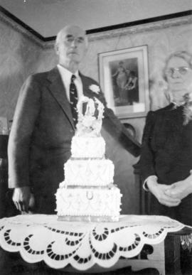 [Mr. H. Appleby and an unidentified woman behind a wedding cake]