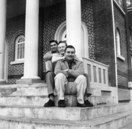 Three men seated on building steps