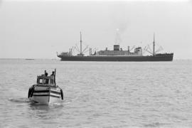 [A fishing boat and a freighter]