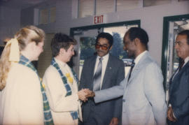 Centennial staff members talking with three unidentified men
