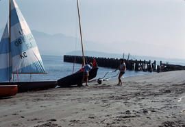 Couple hauling in sailboat at Jericho Beach [Locarno Beach]