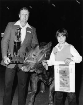 1977 P.N.E. 4-H Club competition winner and P.N.E. 4-H Chairman pose with livestock and prizes