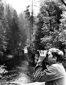 Boy looking through binoculars, Capilano Canyon in background