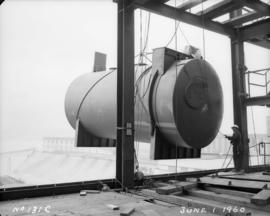 Construction of pan house: tank being hoisted into place
