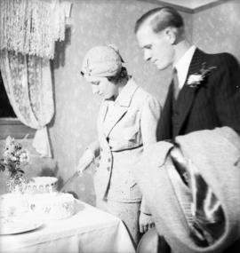 [Unidentified groom and bride cutting wedding cake]