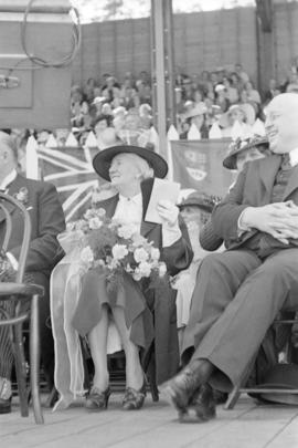 Woman holding flowers seated beside William Aberhart at Golden Jubilee opening ceremonies at Broc...