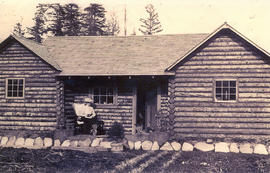 [Woman seated outside log house]