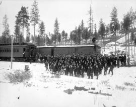 [Men assembled in snow outside railway car for the opening of the C.P.R. branch line between Spen...