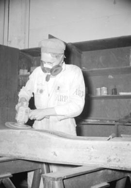 [Worker sanding airplane parts at the Boeing plant on Sea Island]