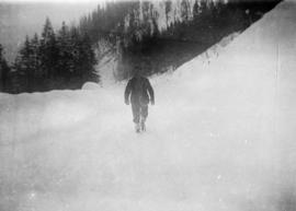Man walking along snowy road, possibly Karl Koenig