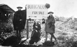 "Three young women beside ""Bungalow for Sale"" sign"