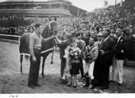 Prize presentation to horse race winner in front of grandstand