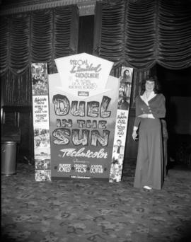 "[Theatre usher standing at a ""Duel in the Sun"" movie poster display]"