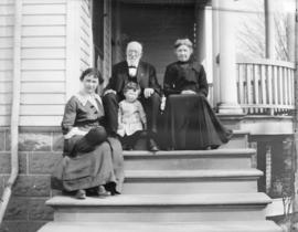 [A man, two women and a child sitting on the steps of a house]