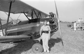 [Female pilot standing beside biplane at airshow]