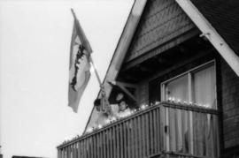 Family on balcony holding Centennial flag