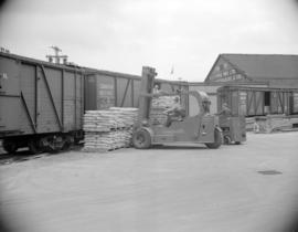 [Men loading goods onto railway cars by forklift at Evans, Coleman, and Evans Ltd.]