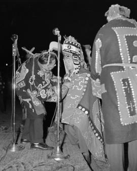 [Lord Alexander wearing a First Nations mask and blanket kneeling before Chief Wiliam Scow at a s...