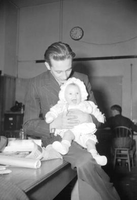 [Portrait of Ray Gardner holding a baby at the Vancouver New-Herald offices]