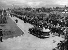 [King George VI and Queen Elizabeth travelling past a crowd-lined road in park]