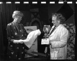 Women holding trophy and award-winning garment in 1957 P.N.E. Home Arts show